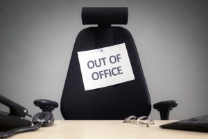 desk chair at office desk with sign that reads out of office employee absence sick days commercial cleaning services cost