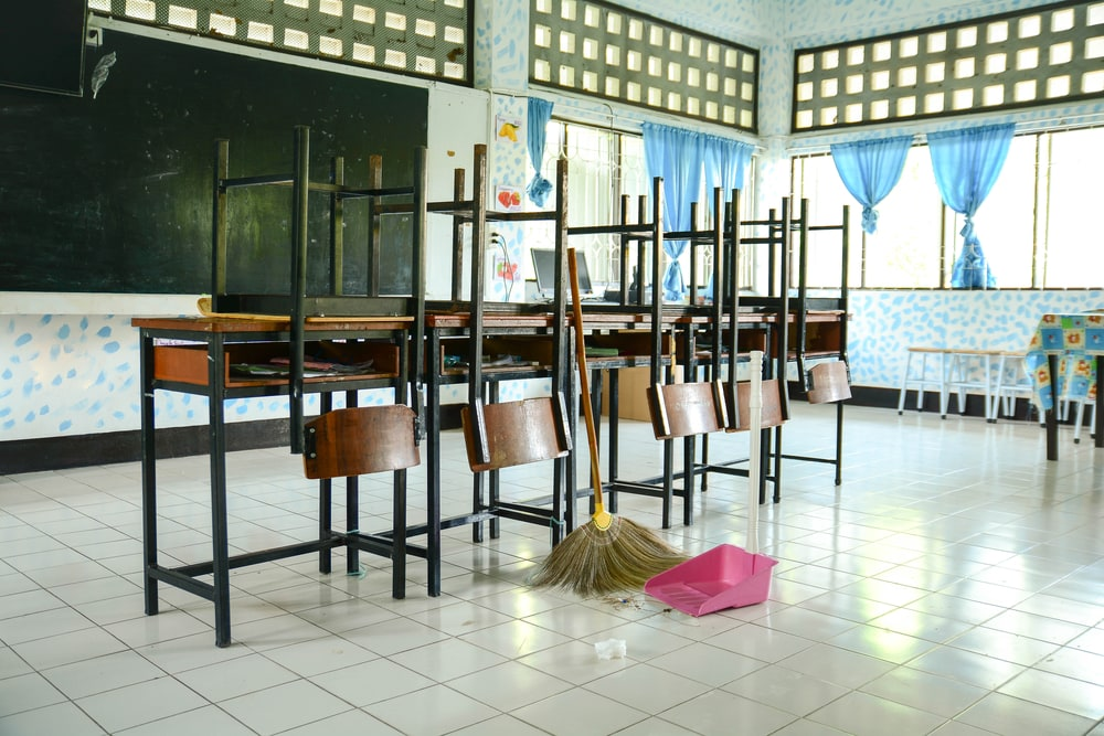 Classroom cleaning with a broom. School cleaning during summer break photo of classroom with chairs on desks and cleaning supplies