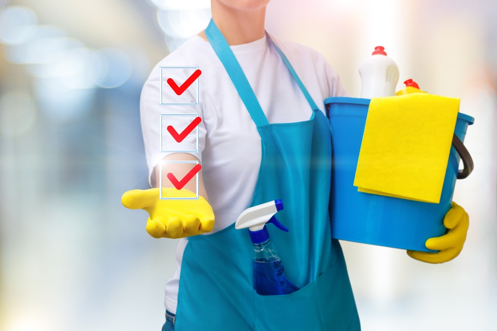Cleaning lady shows a list of completed tasks on blurred background. Summer school cleaning tips tip number 1 plan it out write out create cleaning checklists