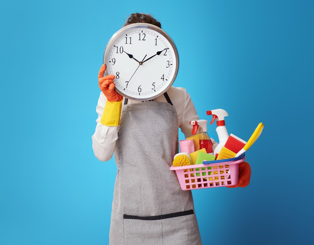 cleaning woman in apron with basket with detergents holding clock in front of face against blue background. Time is money! If cleaning is not in the business plan, you should call a cleaning service. Summer school cleaning tip #3 take your time don't try to do it all at once