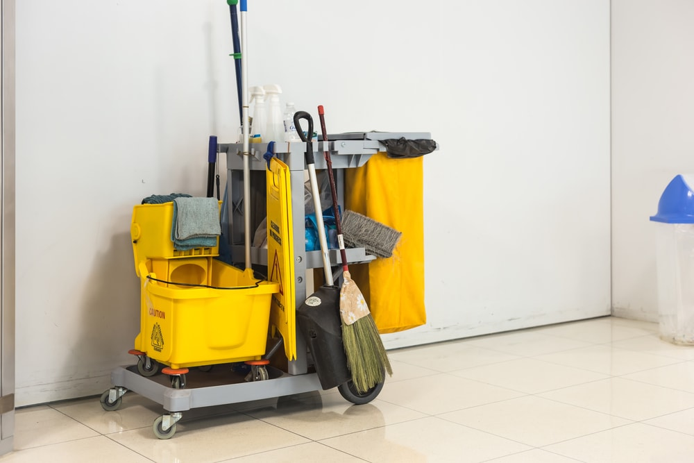 Yellow mop bucket and set of school cleaning equipment