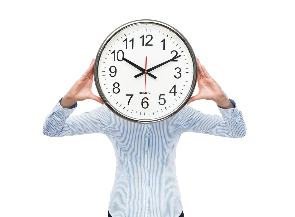 Hiring a commercial cleaning business saves you time woman holding a clock with both hands in front of her face representing saving time